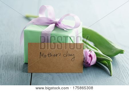 green gift box with purple bow and tulip on blue wood background with mothers day greeting card, romantic photo
