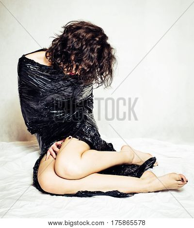 Melancholy model woman confined in black foil