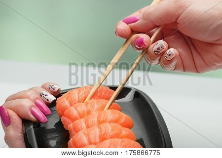 The female hand with magnificent manicure takes sushi with a light-salted salmon from a black ceramic plate by means of wooden sticks