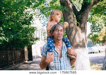 A Little Girl Is Eating Ice Cream Sitting On Her Father's Shoulders.