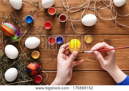 Easter eggs craft. Paint colorful handmade holiday decoration, preparing for happy event. Artist hands draw yellow eggshell, top view on rustic wood background