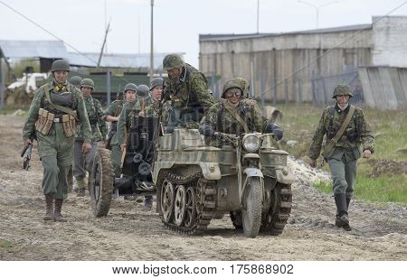 SAINT PETERSBURG, RUSSIA - MAY 05, 2015:  A group of German soldiers with the tractor SdKfz 2, and anti-tank guns moving on the road. Reconstruction of the episode of the great Patriotic war