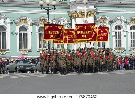SAINT PETERSBURG, RUSSIA - MAY 05, 2015: The group in the form of soldiers of the great Patriotic war with banners of military fronts in rehearsal of parade in honor of Victory Day