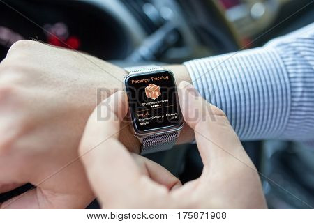 men hands smart touch watch with app tracking delivery package in car