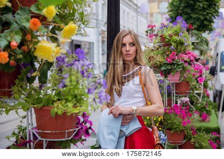 Blonde in the street among the flowers