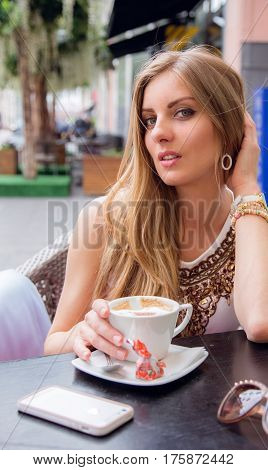 Blonde outdoors with a cup of coffee