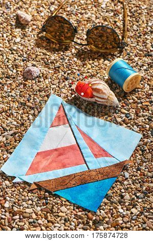 Patchwork block spool of thread pin cushion and sun glasses lie on sea stones of beach