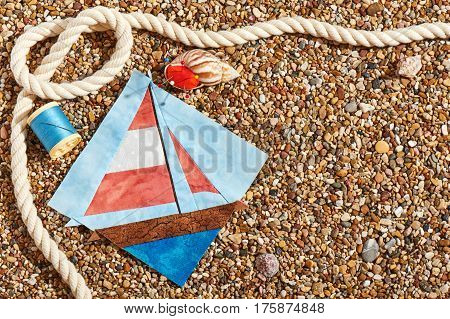 Patchwork block spool of thread pin cushion and rope lie on sea stones of beach