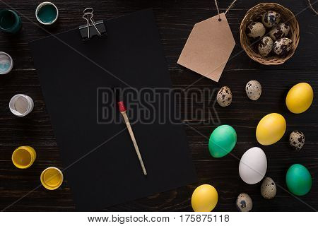 Greeting card with paschal eggs on rustic, wood table. Top view. Copy space
