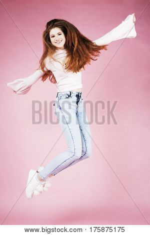 young pretty red hair ginger girl jumping isolated on pink background, lifestyle flying teen people happy smiling concept close up