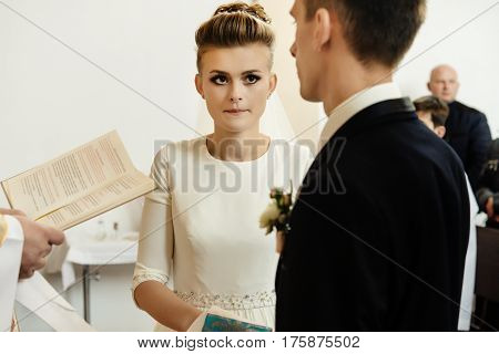 Happy Stylish Bride And Elegant Groom Exchanging Vows At Catholic Wedding Ceremony At Church