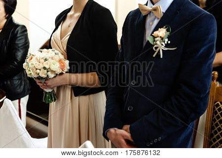 Stylish Chauffeur And Bridesmaid Holding Bouquet At Wedding Ceremony At Church