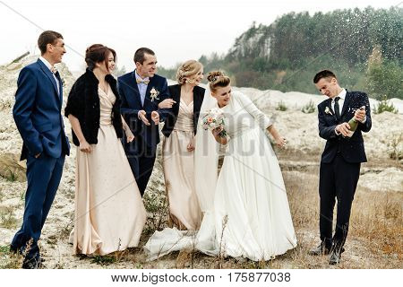 Bride And Groom With Happy Groomsmen And Bridesmaids Having Fun And Popping Champagne, Luxury Weddin
