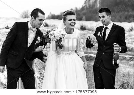 bride and groom with happy groomsmen and bridesmaids having fun and toasting with champagne black and white hilarious moment