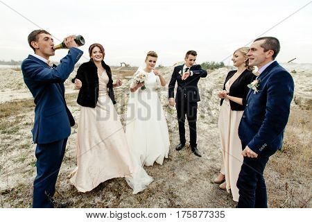 Bride And Groom With Happy Groomsmen And Bridesmaids Having Fun And Toasting With Champagne, Luxury