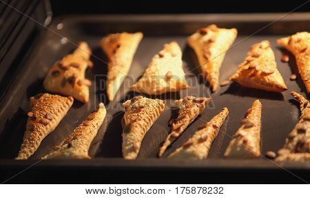 Triangles of puff pastry inside oven baking tray inflate Baked and rouge