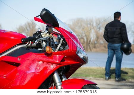 Driver holding helmet in his hand. In focus his sport motorcycle. Photographed besides river.