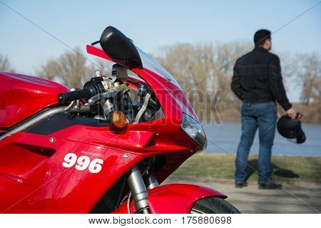 Senta, Serbia: March 4th, 2017. In focus beautiful red Ducati 996s motorcycle, photographed outdoor on a dock in Senta with driver and his helmet holding in his hand