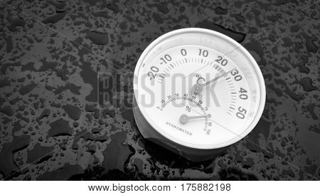 Analog hygrometer putting on a black background filled with drop of water after rain.