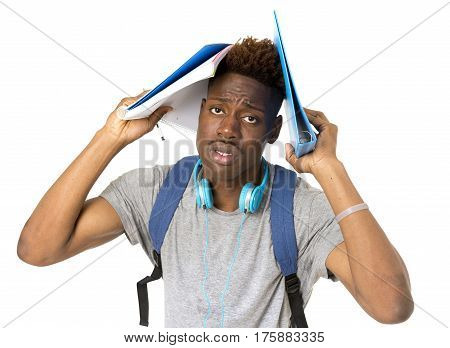 young overworked and stressed university black afro american student on his 20s posing with backpack and notepad isolated background in education stress and hard work concept