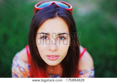 Young charming woman with glasses on tinted hair with beautiful brown eyes with perfect make-up on blurred green background closeup.