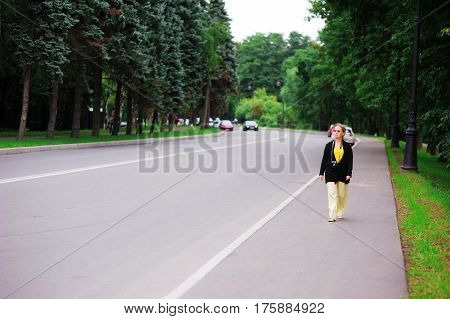 Mature attractive woman in a black cardigan and light trousers with a camera around my neck walking on the side of the road on the background of green trees.