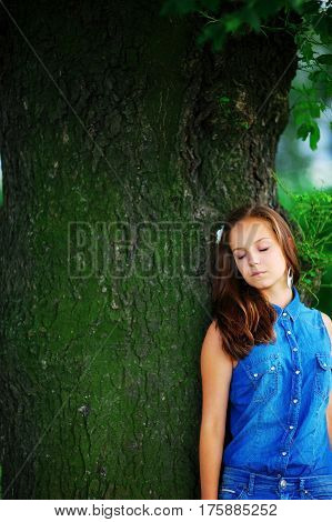 Cute and fragile young woman with closed eyes leaning against a great tree enjoying rest. The concept of unity of man with nature.
