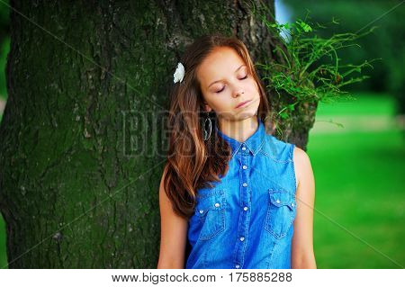 closeup portrait of beautiful woman with flower in hair and eyes closedleaning against a great tree and enjoying the warmth of sunlight during summer holidays and vacations