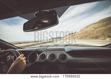 Man driving his sport car on Californian street way