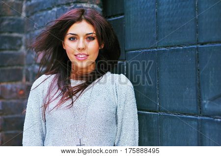 portrait of a beautiful girl with a ragged outer wind hair and a cute smile posing on brick wall background closeup