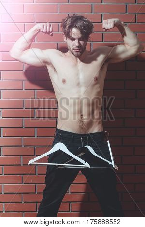 Bearded Muscular Macho Man Hipster With Sexy Body Holds Hangers