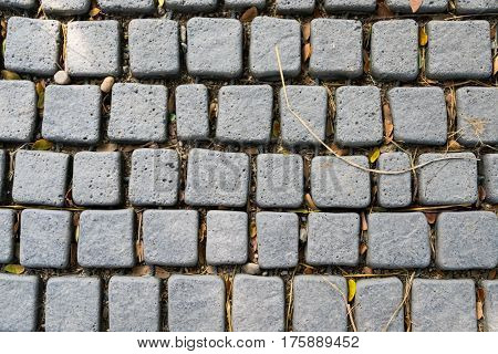 A top view of cobblestone on footpath in grey tone selective focus.