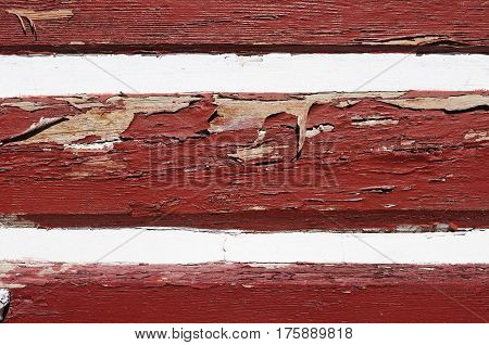 Threadbare wooden wall painted in claret red and white colors