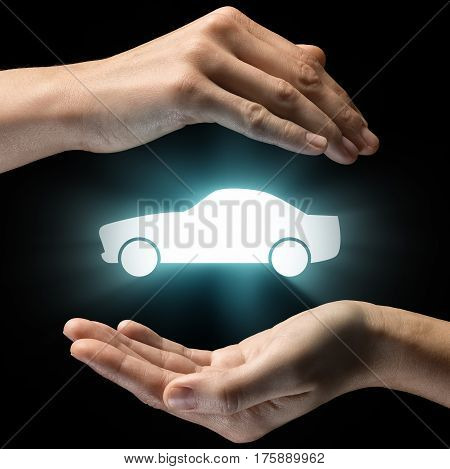 Isolated image of two hands on black background. Car icon in the center as a symbol of car service security insurance. Concept of car service security insurance.