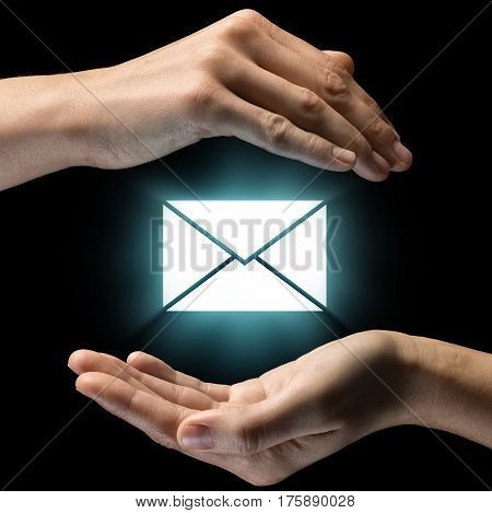 Isolated image of two hands on black background. Envelope icon in the center as a symbol of confidentiality of correspondence. Concept of confidentiality of correspondence.
