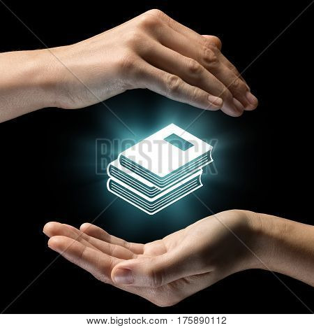 Isolated image of two hands on black background. Pile of books icon in the center as a symbol of library knowledge. Concept of library knowledge.