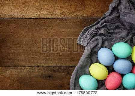 Overhead view of colorful Easter eggs lying over a gray fabric on a wood table top. Flat lay style.