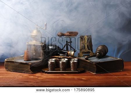 Antiquarian objects on a wooden table in white smoke