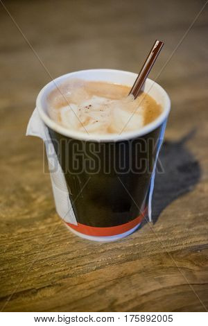 Cup of coffee in paper cup to take away on wood table