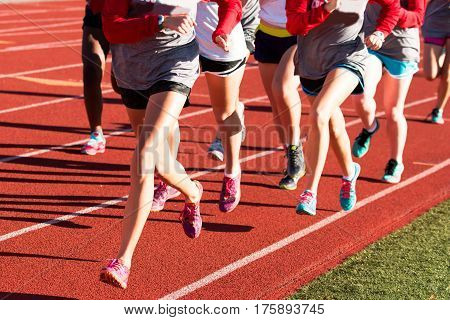 Girls cross country workout running intervals together on a red track while wearing spikes.