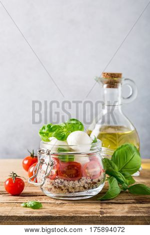 Delicious caprese salad with quinoa, ripe cherry tomatoes and mini mozzarella cheese with fresh basil leaves in glass jar and olive oil. Italian healthy food concept with copy space.