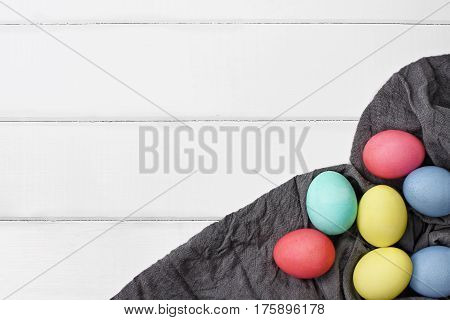 Overhead view of colorful Easter eggs over a wood table top with grey fabric. Flat lay style.