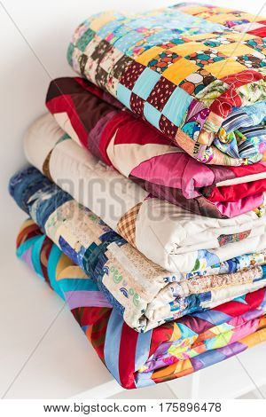magnificent colored patchwork quilt put by a pile on a white court cupboard close up. a concept with scrappy blankets.