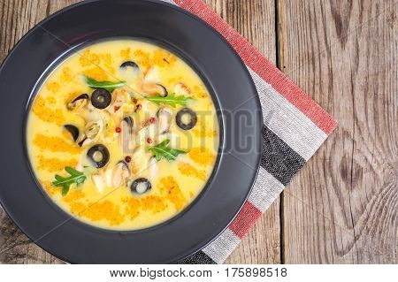 Vegetable soup puree with mussels in black plate on wooden background. Studio Photo