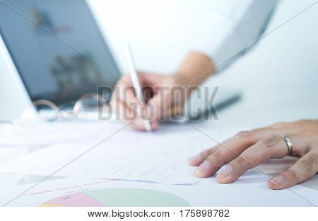 Office worker is analyzing paper and chart infomation