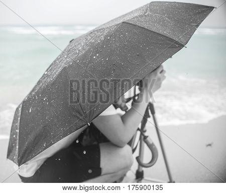 man kneeling under umbrella during a beach rain storm