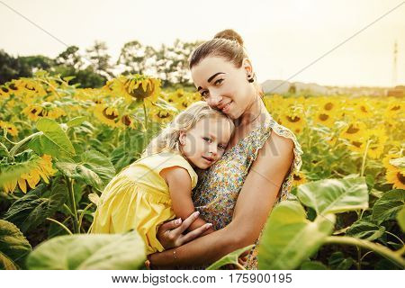 Happy mother with the daughter in the field with sunflowers