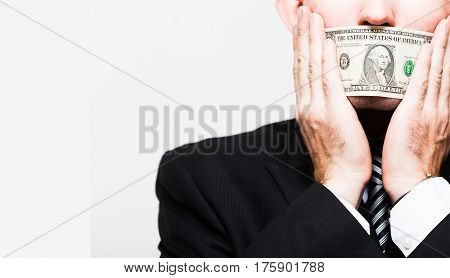 man businessman in a suit with a closed one dollar bills mouth silent for money. the concept of corruption