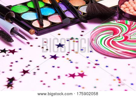Holiday party makeup cosmetics with lollipop and confetti. Shallow depth of field