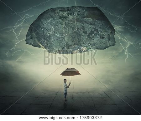 Surrealistic image as a man stand in a foggy street under a huge levitating rock holding an umbrella in hand as a protection from danger. Life pressure and stress concept.